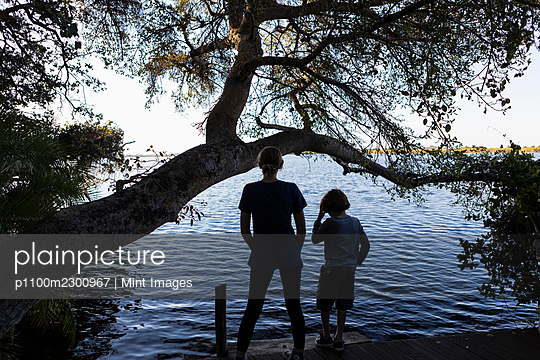Two children on the edge of a waterway, rear view, Okavango Delta - p1100m2300967 by Mint Images
