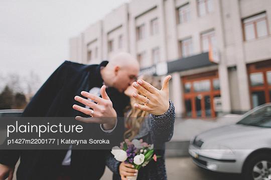 Newlywed couple kissing on street - p1427m2200177 by Kateryna Soroka