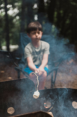 Boy making marshmallow over campfire while sitting on chair in forest - p1166m2034704 by Cavan Images