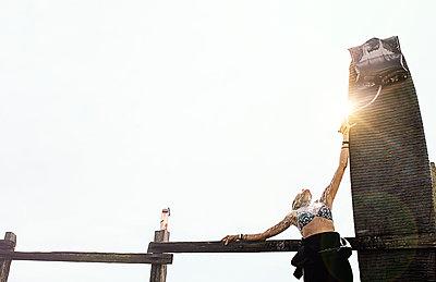 female surfer has post surf shower on longboard - p1166m2152152 by Cavan Images
