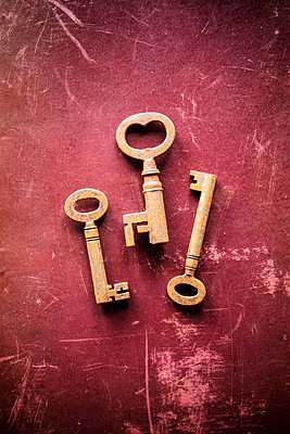 Three rusty old keys lying on a worn and scratched red surface - p1302m2073089 by Richard Nixon