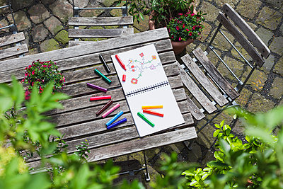 Drawing, sketch book with drawing and coloring pencils on wooden garden table - p300m1140847 by Gaby Wojciech