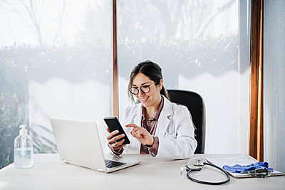 Smiling female doctor using mobile phone while sitting at desk in hospital - p300m2264997 by Eva Blanco