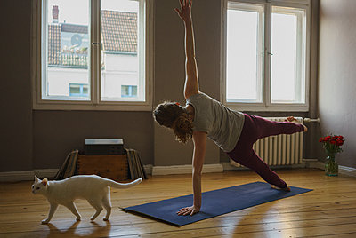 Rear view full length of woman practicing side plank pose on exercise mat by cat at home - p301m1579780 by Halfdark