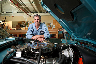 Portrait of mechanic leaning on car - p3722394 by James Godman