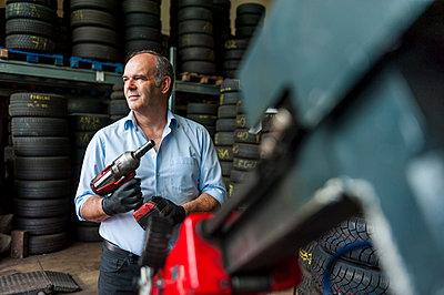 Senior male business owner mechanic holding power tool in repair garage - p429m1174999 by Daniel Ingold