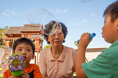 Asian grandmother and grandsons blowing bubbles outdoors - p555m1408699 by Shestock