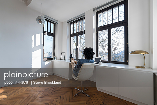Man sitting in minimalist empty room on chair