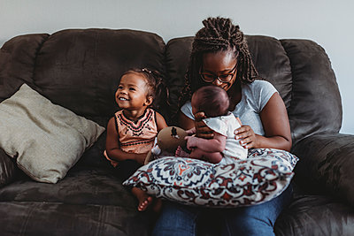 Multiracial family on sofa as mom holds infant next to smiling girl - p1166m2153864 by Cavan Images