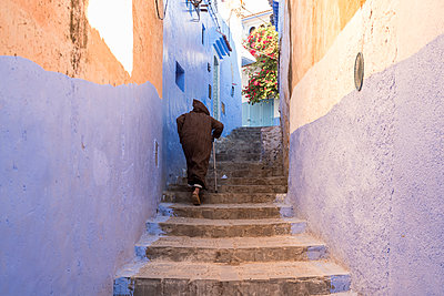 Morocco, Chefchaouen, Local man climbing stairs - p1332m2204607 by Tamboly
