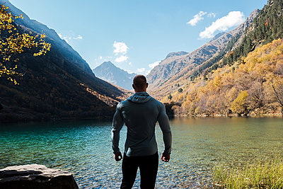 Athletic man is looking at a mountain lake in the Caucasus - p1363m2054118 by Valery Skurydin