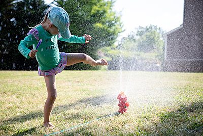 Portrait of a young girl playing in a backyard sprinkler - p1480m2148165 by Brian W. Downs