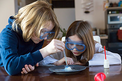 Two children wearing safety glasses using chemistry set at home - p300m1356543 by Sandra Roesch