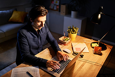 Male freelance worker working late night at home office - p300m2293324 by Bartek Szewczyk