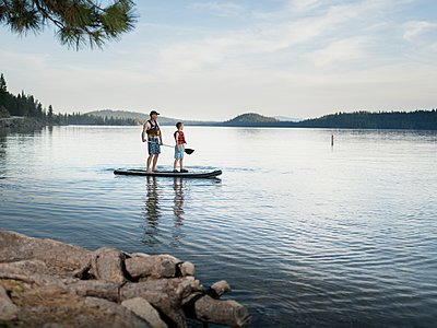 Father and son paddle an SUP on calm waters - p343m1184537 by Melissa L Shelby