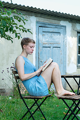 Young woman reading a book in the garden - p427m2134512 by Ralf Mohr