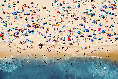 Aerial view of a busy beach with a colourful assortment of umbrellas and towels - p442m883821 by Mike Raabe
