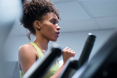 Black woman running on treadmill - p555m1303875 by JGI/Jamie Grill