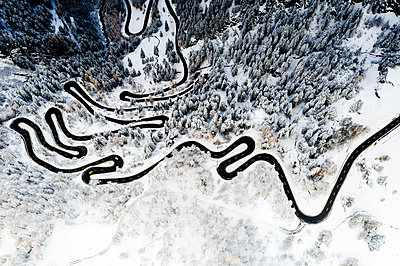 Serpentine road crossing the snowy woods, aerial view, Maloja Pass, Bregaglia Valley, Graubunden, Engadine, Switzerland - p651m2271106 by Roberto Moiola
