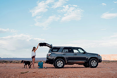 Young woman in remote setting, opening boot of SUV, dog beside her, Mexican Hat, Utah, USA - p924m1580620 by Seth K. Hughes
