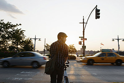 Male cycle messenger waiting to cross busy road - p924m958034f by Matt Dutile
