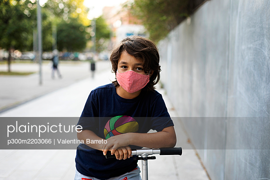 Portrait of boy with scooter in the city wearing protective mask - p300m2203066 by Valentina Barreto
