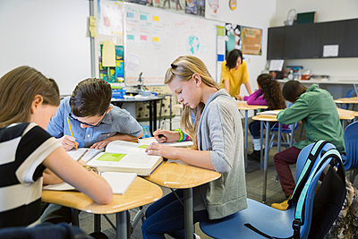 Elementary students studying in classroom - p1192m1016769f by Hero Images