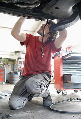 Germany, Ebenhausen, Mechatronic technician working in car garage - p30020017f by Tom Chance