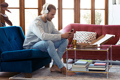 Young man sitting on couch with cell phone and headphones - p300m2114516 by Josep Suria