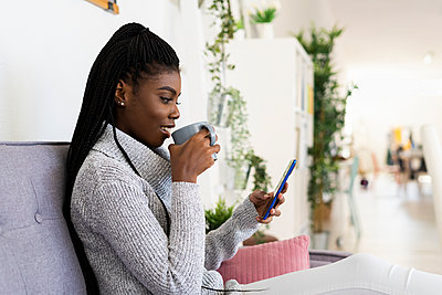 Young woman drinking coffee while text messaging on smart phone at home - p300m2226126 by Giorgio Fochesato