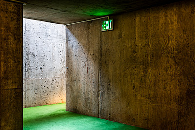 Exit sign in a concrete room with green carpeting - p397m2015241 by Peter Glass