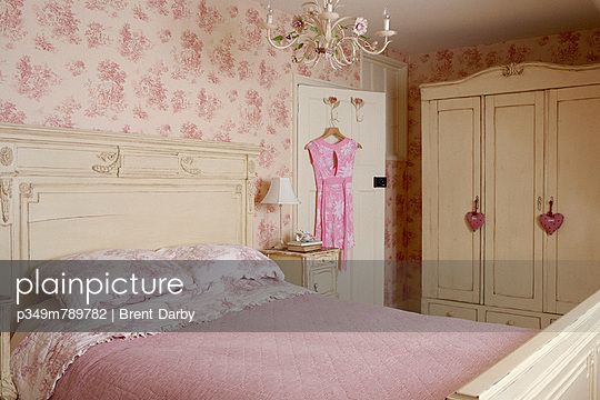 Painted bed and wardrobe in room with co-ordinating wallpaper and bed linen - p349m789782 by Brent Darby