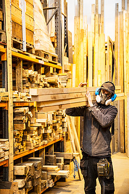 Man wearing ear protectors and dust mask standing in a warehouse, carrying long planks of wood on his shoulder. - p1100m1575732 by Mint Images