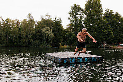Senior man jumping from raft in a lake - p300m2080269 von Gustafsson