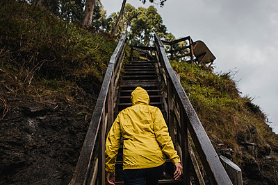 Rear view of woman in raincoat climbing staircase during rainy season - p300m2225348 by David Molina Grande