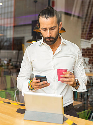 Candid portrait of bearded businessman drinking coffee and using phone inside cafe - p300m2240862 by Jose Carlos Ichiro