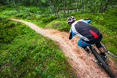 Mountain biker in a fast paced corner in Valadalen, Sweden. - p343m1090336 by Elias Kunosson