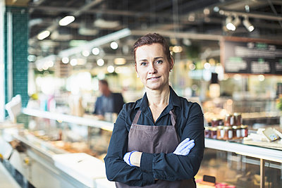 Portrait of confident female owner standing arms crossed in supermarket - p426m1407378 by Kentaroo Tryman