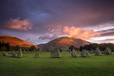 Castlerigg Stone Circle in autumn at sunrise with Blencathra bathed in dramatic dawn light, Lake District National Park, Cumbria, England, United Kingdom, Europe - p871m1197006 by John Potter