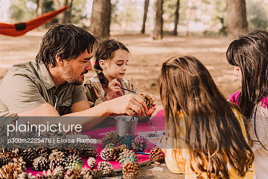 Mature man with daughters decorating while coloring pine cones at picnic table in park - p300m2225476 by Eloisa Ramos