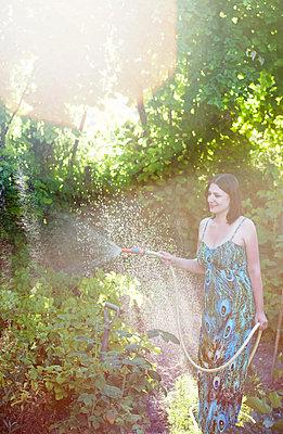 Frau wässert Gartenpflanzen - p1072m2158507 von Neville Mountford-Hoare