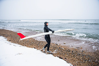 Woman going surfing during winter snow - p1166m2177137 by Cavan Images