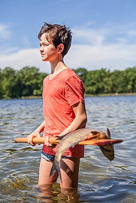 Junge mit gefangenem Fisch am See - p1394m1541463 von benjamin tafel