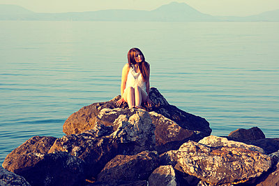 Woman sitting on rock by the sea - p1445m2128457 by Eugenia Kyriakopoulou