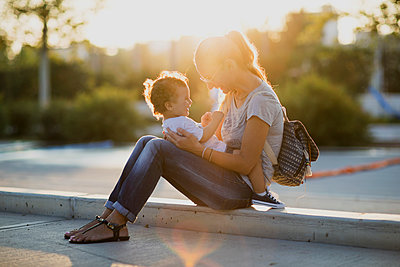 Happy mother sitting with her little son on a square at sunset - p300m2059952 by Nasos Zovoilis