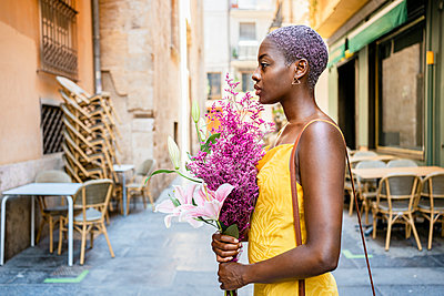 Confident female hipster holding flower bouquet in city - p300m2241642 by Rafa Cortés