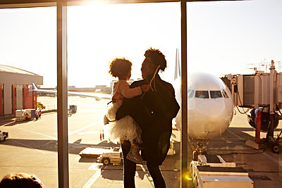 Mother holding daughter at airport - p555m1454093 by Granger Wootz