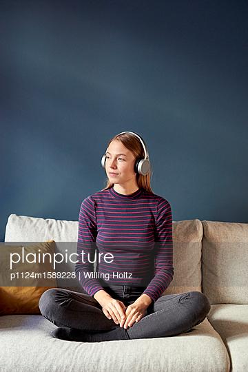 Junge Frau hört Musik über Kopfhörer - p1124m1589228 von Willing-Holtz