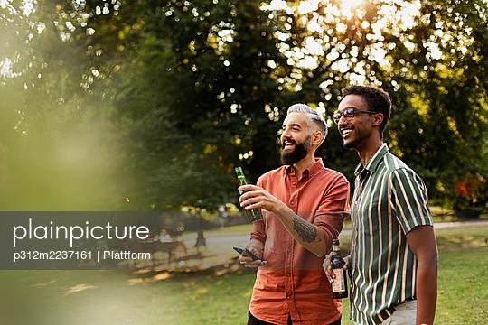 Happy friends having beer in garden - p312m2237161 by Plattform