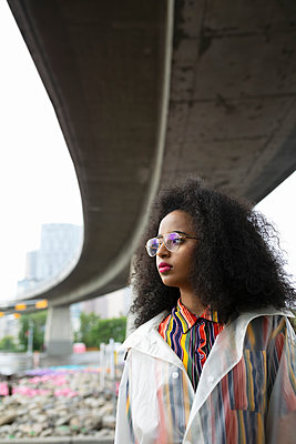 Portrait confident, cool young woman under urban overpass - p1192m2123468 by Hero Images